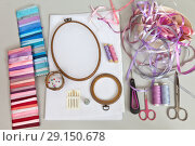 Купить «Accessories for embroidery with satin ribbons: needles, embroidery frame, a set of ribbons, canvases, scissors, thread, pins, thimble and satin ribbons of different colors», фото № 29150678, снято 21 сентября 2018 г. (c) Виктория Катьянова / Фотобанк Лори