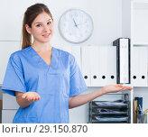 Купить «Female doctor making welcome gesture», фото № 29150870, снято 31 июля 2017 г. (c) Яков Филимонов / Фотобанк Лори