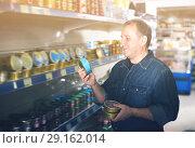 Купить «Portrait of smiling man buying a preserves», фото № 29162014, снято 20 октября 2018 г. (c) Яков Филимонов / Фотобанк Лори