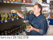 Купить «Portrait of adult man buying a preserves», фото № 29162018, снято 20 октября 2018 г. (c) Яков Филимонов / Фотобанк Лори