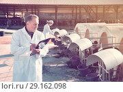 Купить «Quality experts are standing in uniform at the cow farm.», фото № 29162098, снято 24 октября 2017 г. (c) Яков Филимонов / Фотобанк Лори