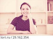 Купить «Positive brown-eyed girl at table», фото № 29162354, снято 9 апреля 2017 г. (c) Яков Филимонов / Фотобанк Лори