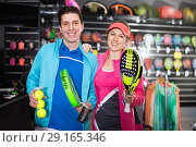 Купить «Sporty couple in sportwear is demonstraiting modern racket and balls for padel», фото № 29165346, снято 7 февраля 2018 г. (c) Яков Филимонов / Фотобанк Лори