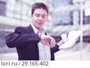 Купить «Businessman hurrying to meeting and watching on wristwatch», фото № 29165402, снято 20 апреля 2017 г. (c) Яков Филимонов / Фотобанк Лори