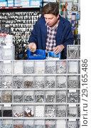 Купить «Man seller with steel details for plumbing», фото № 29165486, снято 4 мая 2017 г. (c) Яков Филимонов / Фотобанк Лори
