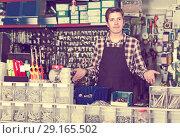 Купить «Man standing near the counter and selling details for plumbing in hardware shop», фото № 29165502, снято 4 мая 2017 г. (c) Яков Филимонов / Фотобанк Лори