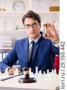 Купить «Young lawyer playing chess to train his court strategy and tacti», фото № 29168442, снято 31 июля 2018 г. (c) Elnur / Фотобанк Лори