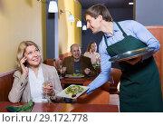 Купить «Positive waiter bringing order to charming smiling mature female», фото № 29172778, снято 22 октября 2018 г. (c) Яков Филимонов / Фотобанк Лори