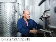 Купить «mature man working in wine fermentation section», фото № 29172818, снято 17 февраля 2019 г. (c) Яков Филимонов / Фотобанк Лори