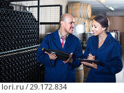 portrait of expert woman standing with clipboard and talking to winemaker in cellar. Стоковое фото, фотограф Яков Филимонов / Фотобанк Лори