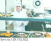 Купить «Portrait of middle aged man baker with tasty cakes smiling in bakery», фото № 29172922, снято 22 апреля 2017 г. (c) Яков Филимонов / Фотобанк Лори