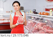 Купить «Positive young seller demonstrating meat in shop», фото № 29173046, снято 22 июня 2018 г. (c) Яков Филимонов / Фотобанк Лори