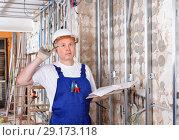 Купить «Focused construction worker inspecting room and planning upcoming repairs», фото № 29173118, снято 28 мая 2018 г. (c) Яков Филимонов / Фотобанк Лори