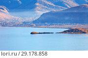 "Купить «The southern tip of Lake Baikal. The Shamansky Cape (Cape Shaman) is a sacred place for the Buryats, called the ""scary stone"". Now this cape is a symbol of the town of Slyudyanka and a favorite tourist destination», фото № 29178858, снято 30 сентября 2018 г. (c) Виктория Катьянова / Фотобанк Лори"