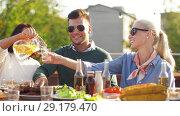 Купить «happy friends eating and drinking at rooftop party», видеоролик № 29179470, снято 26 сентября 2018 г. (c) Syda Productions / Фотобанк Лори