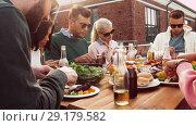 Купить «friends having dinner or bbq party on rooftop», видеоролик № 29179582, снято 26 сентября 2018 г. (c) Syda Productions / Фотобанк Лори