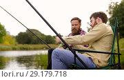 Купить «friends with smartphone and beer fishing on lake», видеоролик № 29179718, снято 28 сентября 2018 г. (c) Syda Productions / Фотобанк Лори