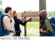 Купить «hiking friends with backpacks at signpost», фото № 29183902, снято 31 августа 2014 г. (c) Syda Productions / Фотобанк Лори