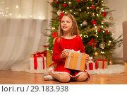 Купить «smiling girl with christmas gift at home», фото № 29183938, снято 22 декабря 2017 г. (c) Syda Productions / Фотобанк Лори