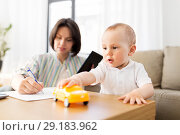 Купить «baby playing with car and mother working at home», фото № 29183962, снято 12 мая 2018 г. (c) Syda Productions / Фотобанк Лори