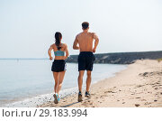 Купить «couple in sports clothes running along on beach», фото № 29183994, снято 1 августа 2018 г. (c) Syda Productions / Фотобанк Лори