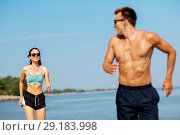 Купить «couple with earphones running along on beach», фото № 29183998, снято 1 августа 2018 г. (c) Syda Productions / Фотобанк Лори