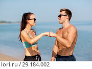 Купить «happy couple in sports clothes and shades on beach», фото № 29184002, снято 1 августа 2018 г. (c) Syda Productions / Фотобанк Лори