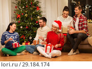 Купить «friends celebrating christmas and opening presents», фото № 29184174, снято 17 декабря 2017 г. (c) Syda Productions / Фотобанк Лори