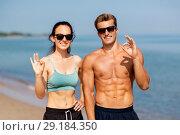 Купить «couple of athletes in shades on beach showing ok», фото № 29184350, снято 1 августа 2018 г. (c) Syda Productions / Фотобанк Лори