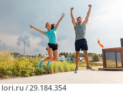 Купить «happy couple in sports clothes jumping on beach», фото № 29184354, снято 1 августа 2018 г. (c) Syda Productions / Фотобанк Лори