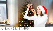 Купить «woman in santa helper hat with christmas ball», фото № 29184406, снято 15 августа 2013 г. (c) Syda Productions / Фотобанк Лори