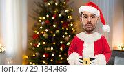 Купить «surprised man in santa clothes over christmas tree», фото № 29184466, снято 15 января 2016 г. (c) Syda Productions / Фотобанк Лори