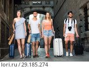 Купить «Four friends are walking together with luggage», фото № 29185274, снято 22 июня 2017 г. (c) Яков Филимонов / Фотобанк Лори
