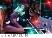 Купить «Excited people playing enthusiastically laser tag game», фото № 29185410, снято 27 августа 2018 г. (c) Яков Филимонов / Фотобанк Лори