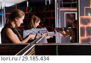Купить «Guys and girls in vests and with laser pistols playing lasertag game in labyrinth», фото № 29185434, снято 27 августа 2018 г. (c) Яков Филимонов / Фотобанк Лори