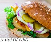 Купить «Image of burger with chicken cutlet, cucumber, lettuce and onion», фото № 29185670, снято 22 октября 2018 г. (c) Яков Филимонов / Фотобанк Лори