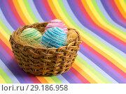 Купить «Easter eggs in wicker basket on a striped colorful background. Easter eggs decoration», фото № 29186958, снято 21 ноября 2018 г. (c) Владимир Пойлов / Фотобанк Лори