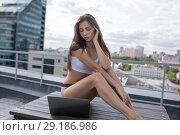 Купить «Young woman in a white top and panties sitting on the roof and using laptop.», фото № 29186986, снято 31 августа 2018 г. (c) Женя Канашкин / Фотобанк Лори