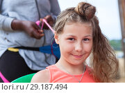 Купить «Happy and smiling girl looking at camera when hairdresser making afro bunches», фото № 29187494, снято 19 июля 2018 г. (c) Кекяляйнен Андрей / Фотобанк Лори