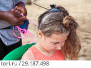 Купить «European pretty girl sitting on chair while hair braider has cornrow procces», фото № 29187498, снято 19 июля 2018 г. (c) Кекяляйнен Андрей / Фотобанк Лори