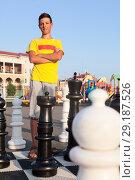 Купить «Молодой человек стоит на шахматном поле сложив руки на груди, игра в шахматы на улице», фото № 29187526, снято 26 июля 2018 г. (c) Кекяляйнен Андрей / Фотобанк Лори