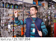 Купить «serious male choosing fishing rod for fishing in the sports shop», фото № 29187994, снято 16 января 2018 г. (c) Яков Филимонов / Фотобанк Лори