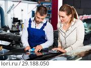 Купить «Serious car painter discussing with female client, picking up color of paint in auto repair shop», фото № 29188050, снято 4 апреля 2018 г. (c) Яков Филимонов / Фотобанк Лори
