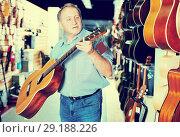Купить «male choosing acoustic guitar», фото № 29188226, снято 18 сентября 2017 г. (c) Яков Филимонов / Фотобанк Лори