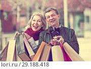 Купить «Mature spouses with shopping bags outdoor», фото № 29188418, снято 14 декабря 2018 г. (c) Яков Филимонов / Фотобанк Лори