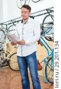Купить «Man choosing sports bicycle with characteristic», фото № 29201134, снято 14 мая 2018 г. (c) Яков Филимонов / Фотобанк Лори