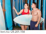 Купить «Young couple planning to surf, choosing boards and surfing suits in beach club», фото № 29201158, снято 30 апреля 2018 г. (c) Яков Филимонов / Фотобанк Лори