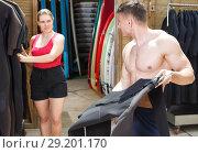 Купить «Sports guy surfer choosing surfing suit for rent», фото № 29201170, снято 30 апреля 2018 г. (c) Яков Филимонов / Фотобанк Лори