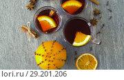 Купить «glasses of hot mulled wine with orange and spices», видеоролик № 29201206, снято 7 октября 2018 г. (c) Syda Productions / Фотобанк Лори