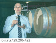 Купить «Confident winemaker offering glass of white sparkling wine for tasting in wine cellar», фото № 29206422, снято 22 января 2018 г. (c) Яков Филимонов / Фотобанк Лори